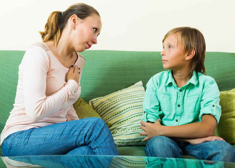 Mother with son having a serious conversation on sofa