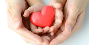 Photo of adult holding a child's hand holding a heart, symbolizing the support of social and emotional learning